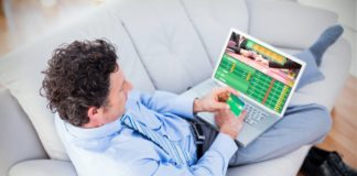man relaxing on the couch placing a sports bet using his laptop